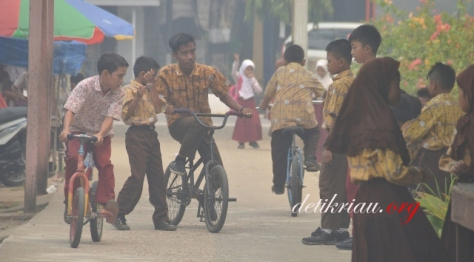 Meski kabut asap tampak cukup pekat, pelajar di SDN 015 Tembilahan masih beraktifitas seperti biasa. bahkan anak-anak pelajar sekolah tingkat dasar ini tidak tampak mengenakan masker pelindung. Foto: Mirwan