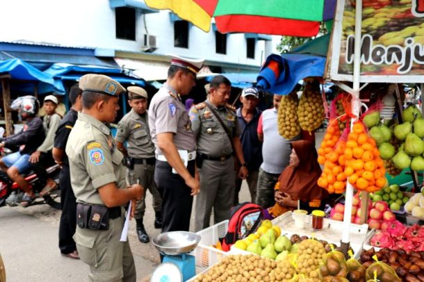 Petugas gabungan saat memberikan teguran kepada pedagang di jalan jendral sudirman Tembilahan yang mempergunakan lokasi berdagang diluar ketentuan aturan