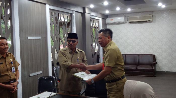 Kepala Dinas Komunikasi, Informatika, Persandian dan Statistik Kabupaten Indragiri Hilir H.M. Taher) (berkopiah) saat menerima penyerahan izin prinsip bagi G FM di Pekanbaru