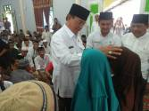 Didampingi Camat Gaung, Nurmansyah (kanan), Bupati Inhil HM Wardan tampak mengelus kepala salah seorang anak yatim