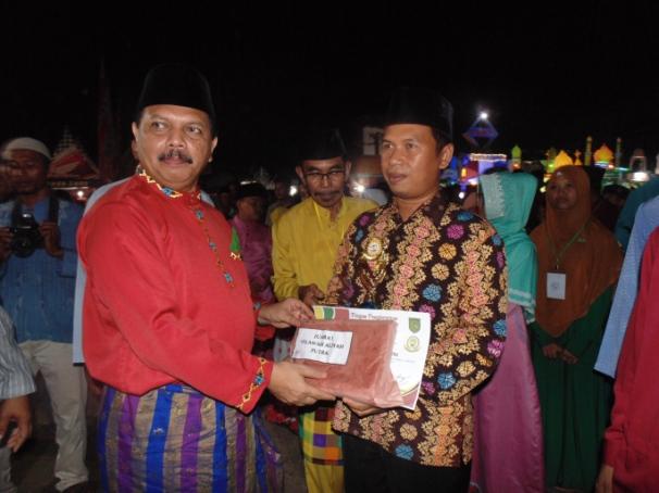 Sekda Inhil H. Said Syarifuddin menyerahkan hadiah kepada Khairuddin sebagai peserta juara pertama cabang Tilawah Dewasa Putra pada MTQ ke 38 Kecamatan Tempuling Tahun 2017