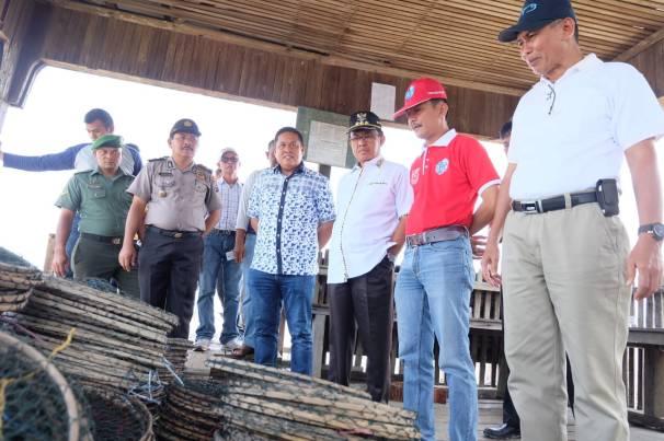 Dari kanan: Kadis KP Inhil Muchtar T, Camat Tanah Merah Yuliargo dan Bupati Inhil HM Wardan memeriksa sejumlah alat tangkap kepiting yang akan diserahkan kepada para nelayan kecil